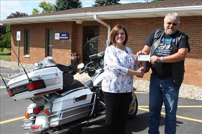Motorcycle enthusiasts from near and far gathered at The Inn Between Saloon in Port Hope, MI for the annual Dillinger Ride on May 27th. Pictured above, ABATE Region 7 Chairman Tim Polk (right) presents United Hospice Service representative Becky Heminger with a donation for the hospice program.