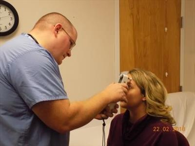Joshua White, M.D., Emergency Department Medical Director demonstrates the use of the tonometer on Stacey Kadar, Occupational Health Nurse of Dow AgroSciences