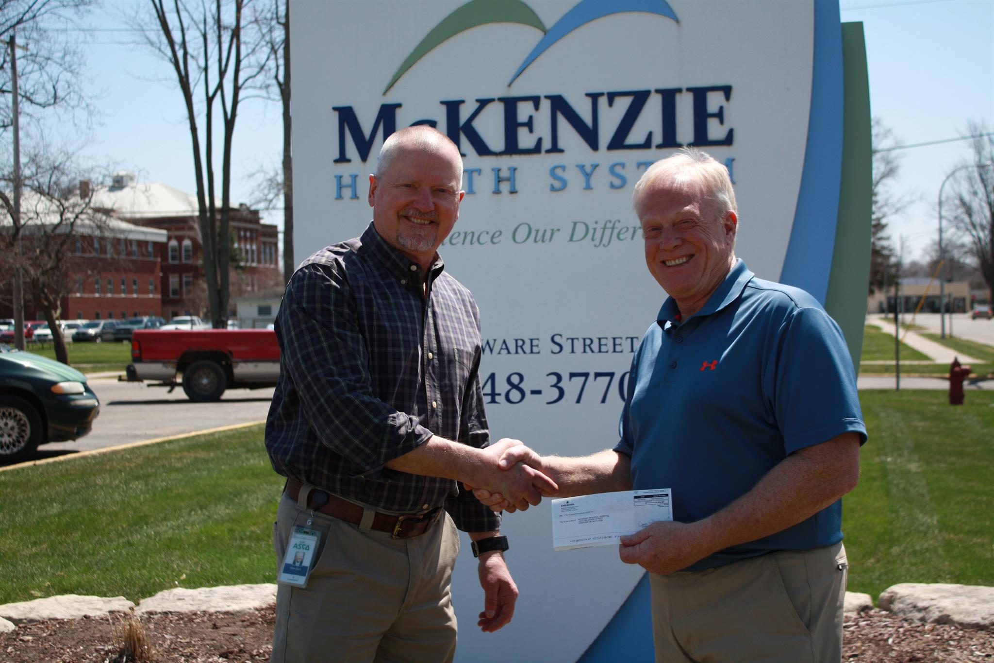 Mike Bach (left), Director of Operations at Numatics presents check to Steve Barnett, DHA, CRNA, FACHE, President/CEO at McKenzie Health System.